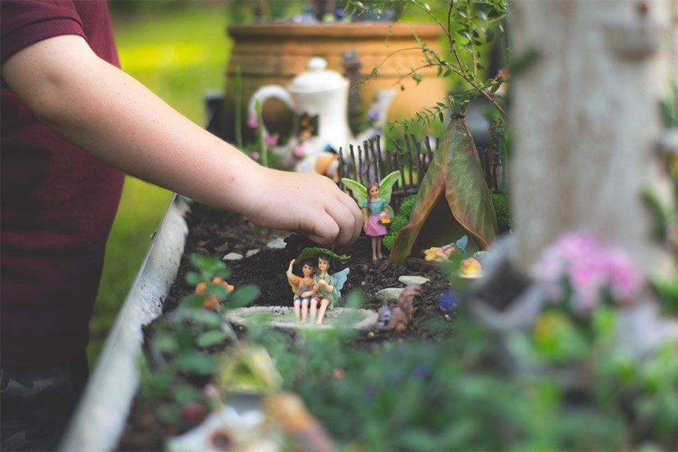 A child playing in their fairy garden